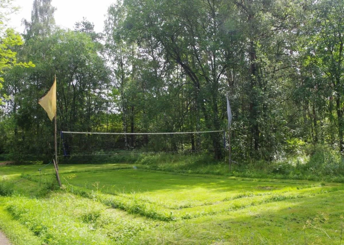 Verkkotolpissa hulmuavat urheilujuhlan kunniaksi liput. Kentälle on nurmikkoon leikattu kahden kenttäkoon rajat.