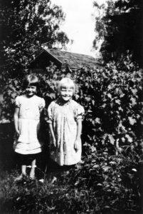 """Kaksi Pyötsaaren tyttöä, Leila Koponen ja Aune Kurki. Leningeistä päätellen kuva on otettu vuonna 1936. Leilan puku on Elisan äidin ompelema, valkoista voileeta. Aunen sininen ja kukallinen puku lainekreppiä """"kreponkia"""", Vilniemellä ommeltu. Leila Koposen arkisto."""